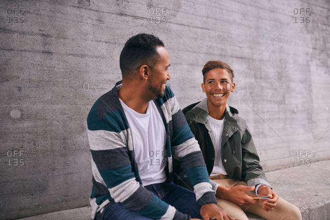 Cheerful father and son looking each other face to face while sitting against wall at playground