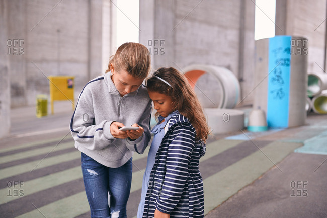 Sisters using mobile phone while standing on footpath at playground
