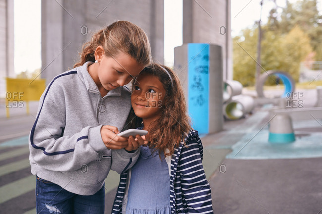 Smiling sisters using mobile phone while standing on footpath at playground