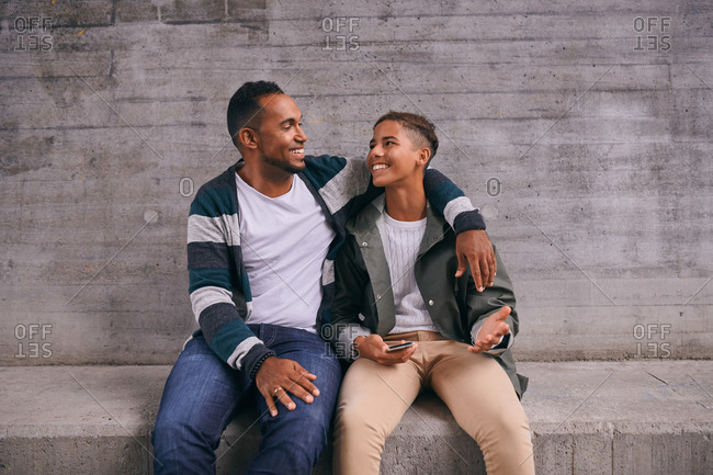 Cheerful father and son looking each other face to face while sitting against wall