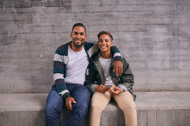 Portrait of cheerful father and son sitting against wall