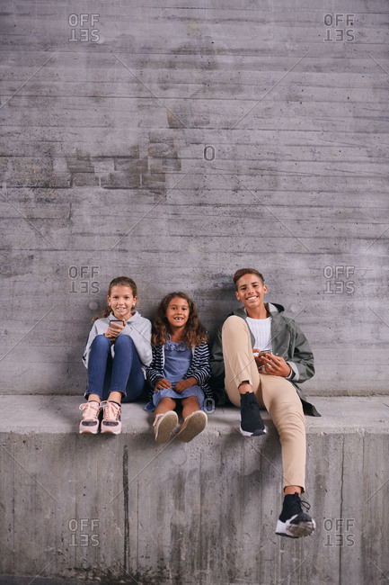 Full length portrait of happy siblings sitting side by side against wall at playground