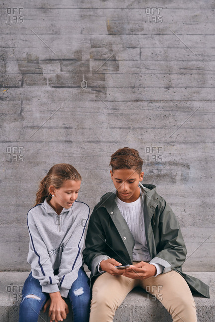 Siblings using mobile phone while sitting against wall