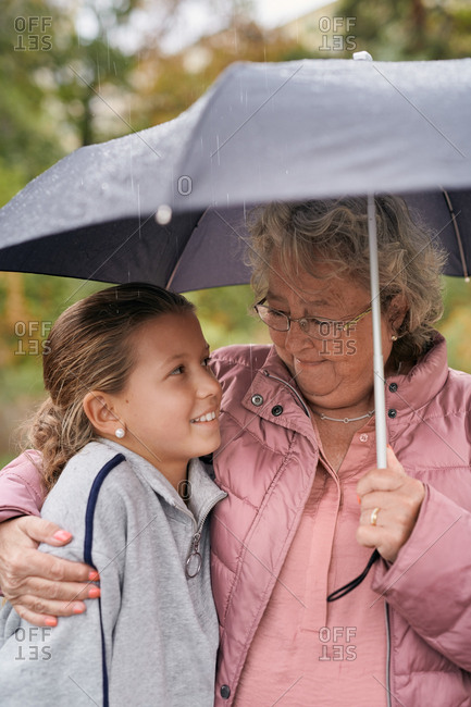 Grandmother embracing granddaughter while sharing umbrella with her in park during rainy season