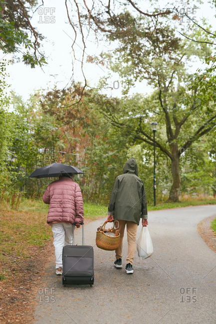 Rear view of grandmother and grandson with luggage walking on road in park during rainy season