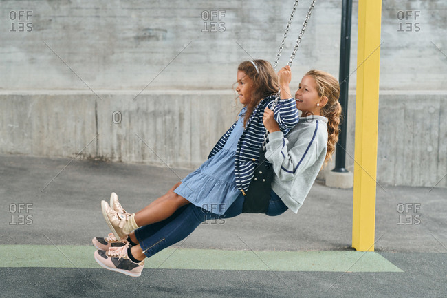 Full length of carefree sisters swinging together on swing at playground