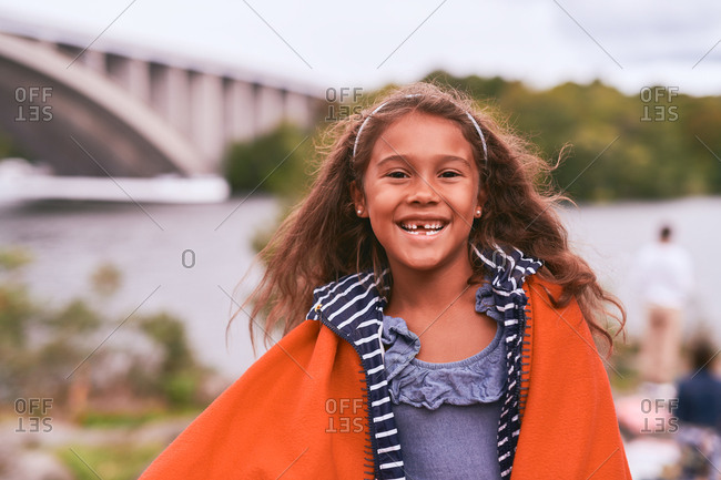 Portrait of cheerful girl with orange blanket standing in park during picnic