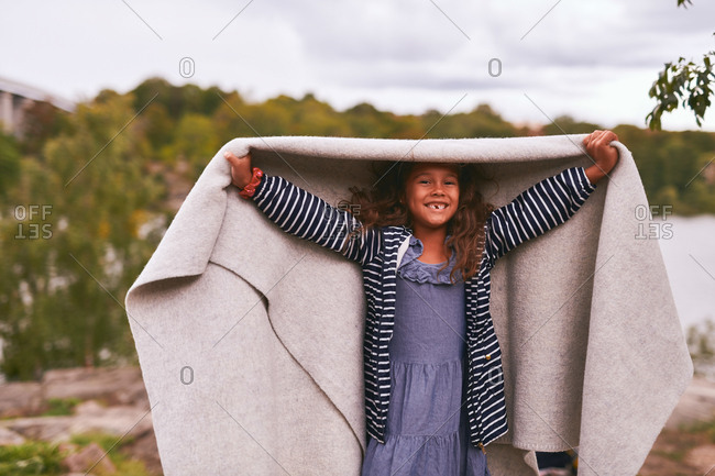 Portrait of cheerful girl holding blanket while standing in park during picnic