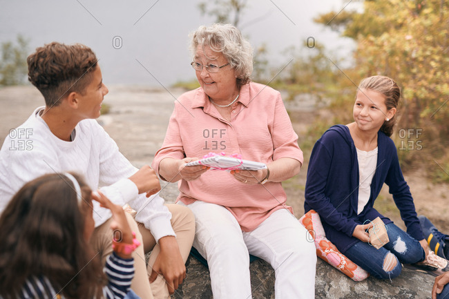 Happy grandmother giving gift to grandson while sitting with granddaughters in park during picnic
