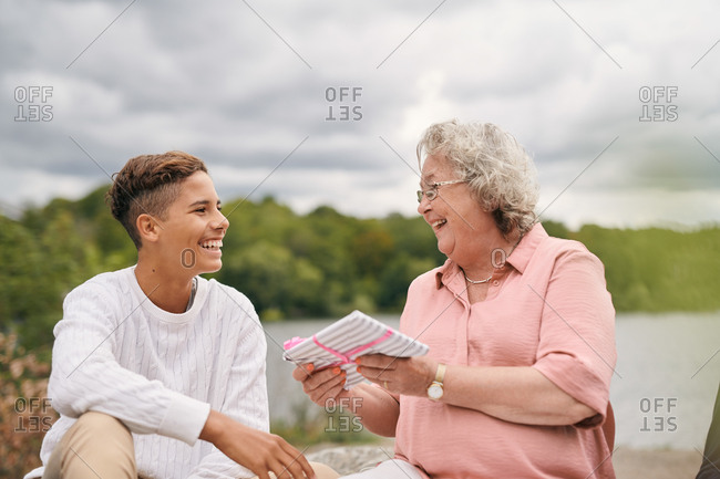 Cheerful grandmother giving gift to grandson in park on lakeshore during picnic