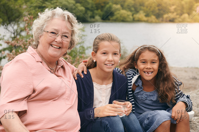 Portrait of smiling granddaughters and grandmother sitting on lakeshore in park