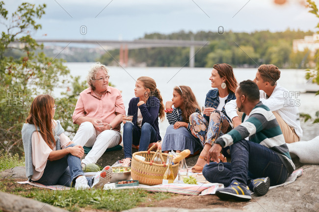 Family and friends looking at senior woman while sitting on lakeshore in park