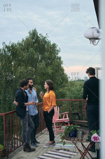 Full length of friends talking while standing on terrace during social gathering