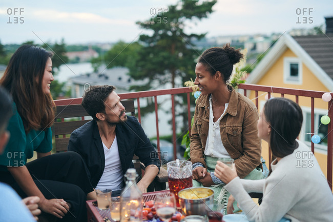 Happy friends talking while sitting on terrace during social gathering