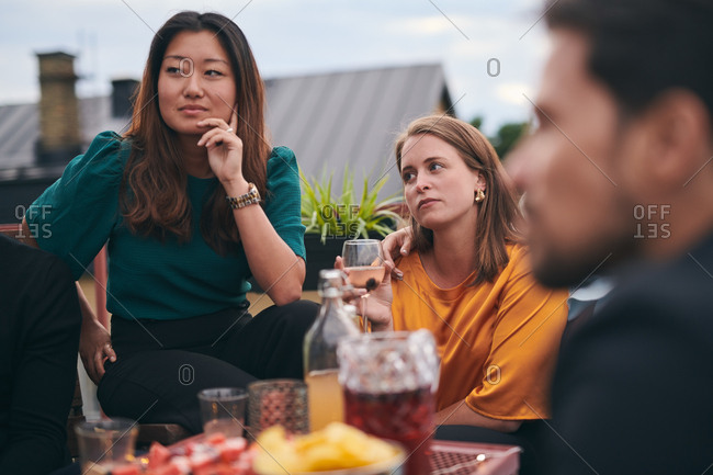 Female friends listening while looking away on terrace during social gathering