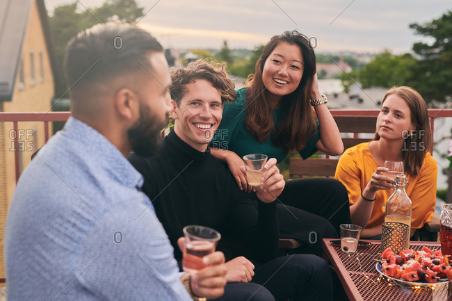 Cheerful friends enjoying social gathering on terrace during sunset