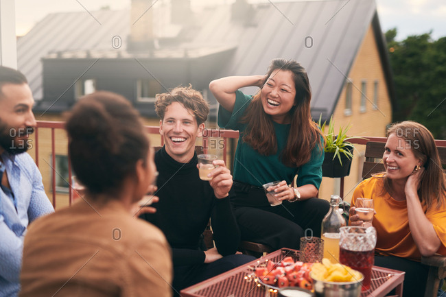 Cheerful friends talking while enjoying social gathering on terrace