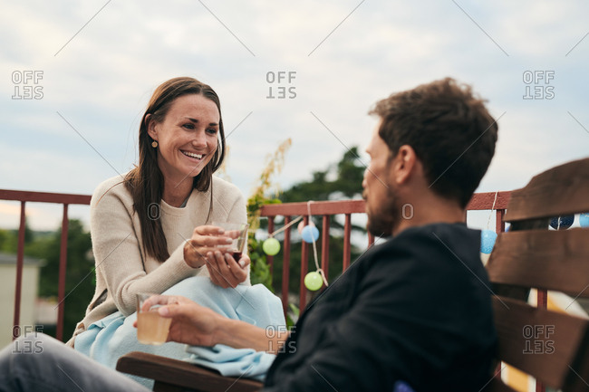Cheerful woman talking with male friend while holding drink on terrace during social gathering