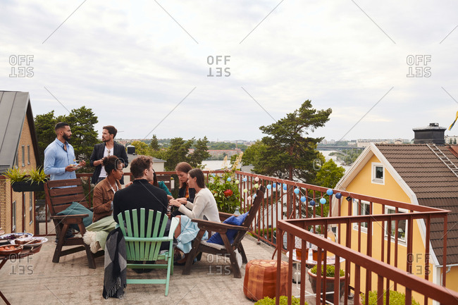 Friends talking while spending leisure time on terrace against sky