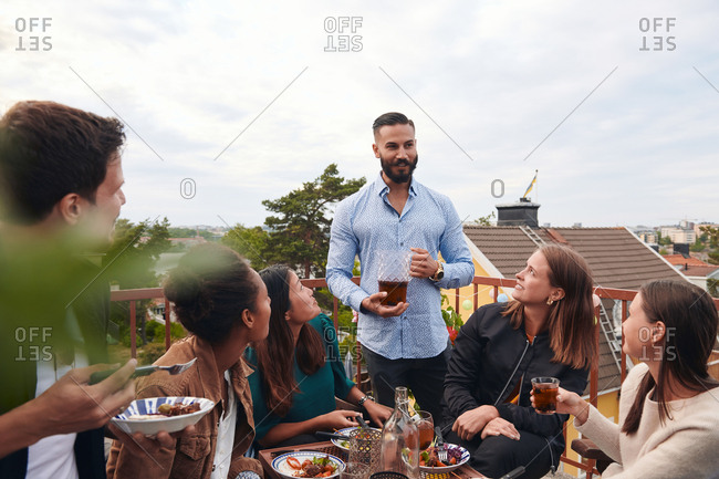Man talking with friends while holding drink on terrace