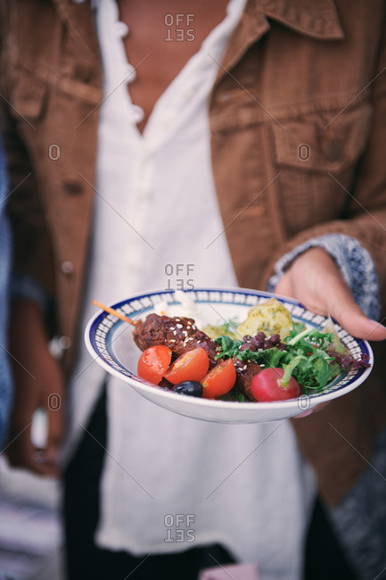 Midsection of woman holding meal in plate during social gathering on terrace
