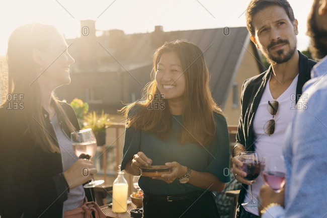 Cheerful friends having social gathering on terrace during sunset
