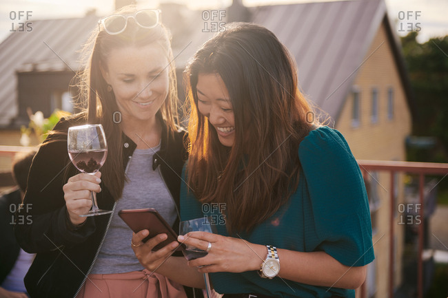 Cheerful woman showing her mobile phone to female friend on terrace during sunset