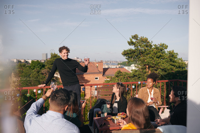 Smiling young man raising toast during social gathering on terrace