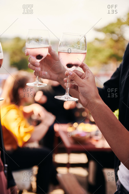 Cropped hands of friends holding wineglasses during social gathering on terrace