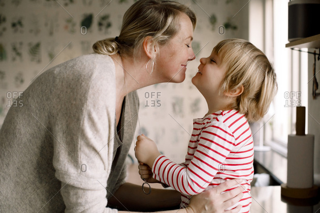 Side view of playful mother and daughter spending leisure time in kitchen at home