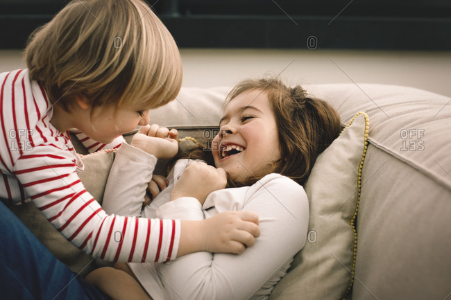 Playful girl tickling cheerful sister on couch at home