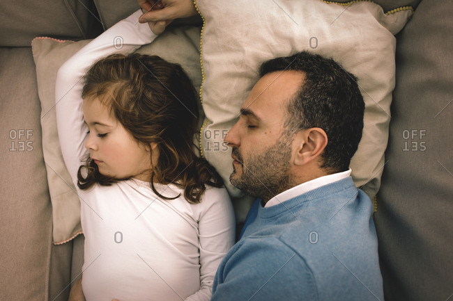 Directly above shot of father and daughter napping on couch at home