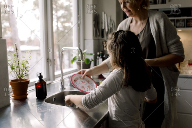 Daughter helping mother in kitchen at home