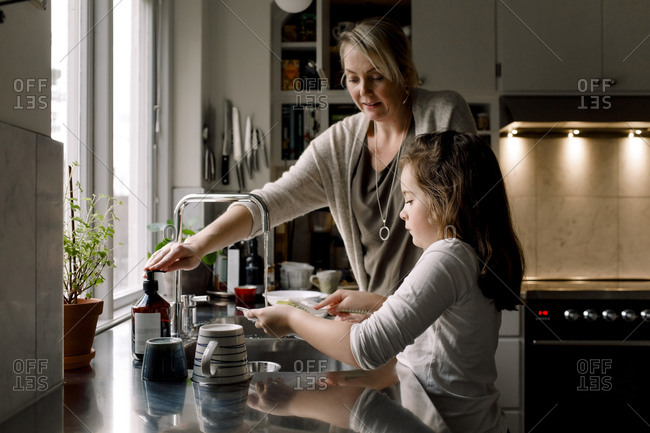 Daughter washing dishes while standing by mother in kitchen at home