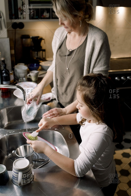 High angle view of mother and daughter working in kitchen at home
