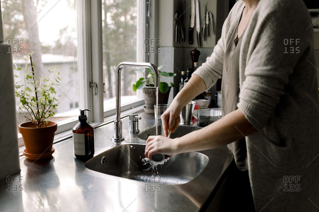 Midsection of woman cleaning cup in kitchen sink at home