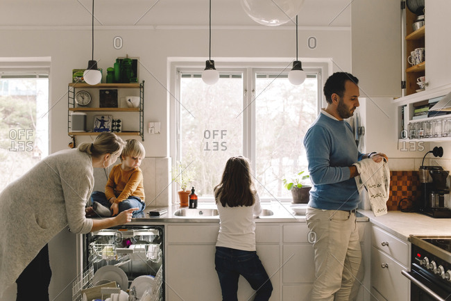 Family of four working in kitchen at home