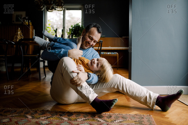 Full length of happy playful father carrying daughter while sitting on hardwood floor at home