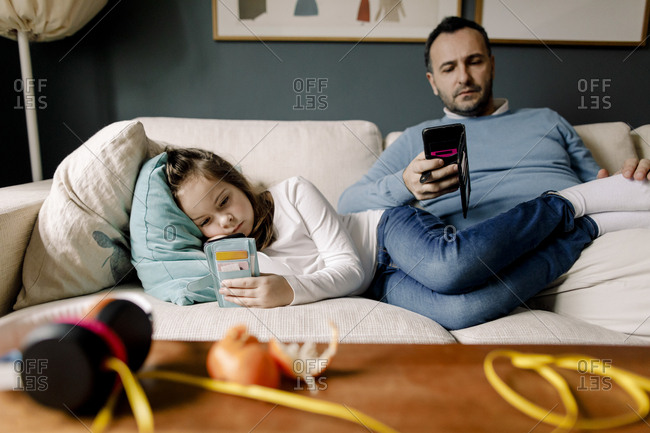 Father and daughter using mobile phones on couch in living room