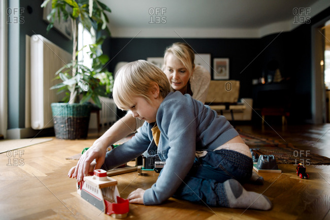 Mother and daughter playing with toy train on hardwood floor in living room at home