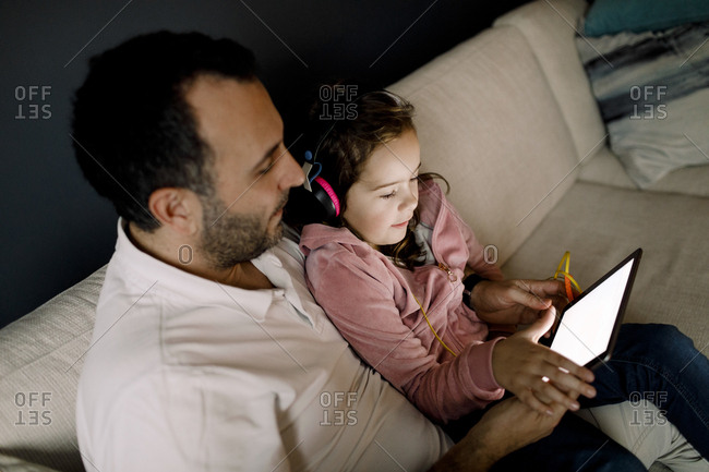 High angle view of father assisting daughter in using digital tablet on couch at home