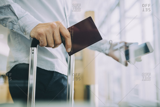 Midsection of businessman holding passport at airport