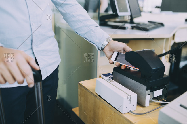 Midsection of businessman scanning ticket on smart phone at airport check-in counter
