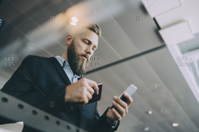 Low angle view of businessman using smart phone while holding passport at airport