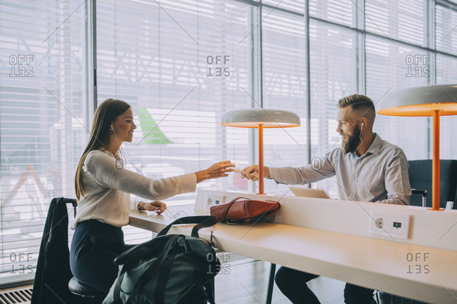 Smiling businessman giving charger to young businesswoman while sitting at airport