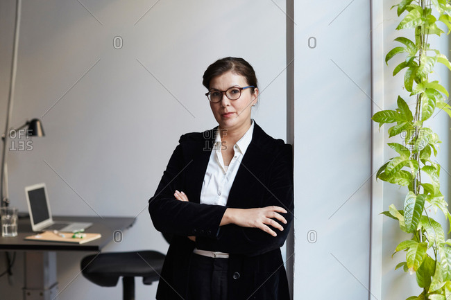 Portrait of confident mature businesswoman leaning on wall in office