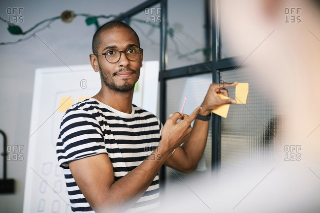 Creative businessman showing adhesive note to colleague in office