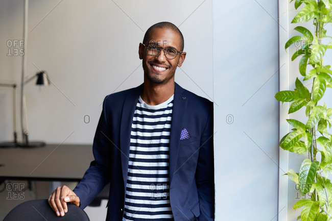 Portrait of smiling male entrepreneur standing by wall in creative office