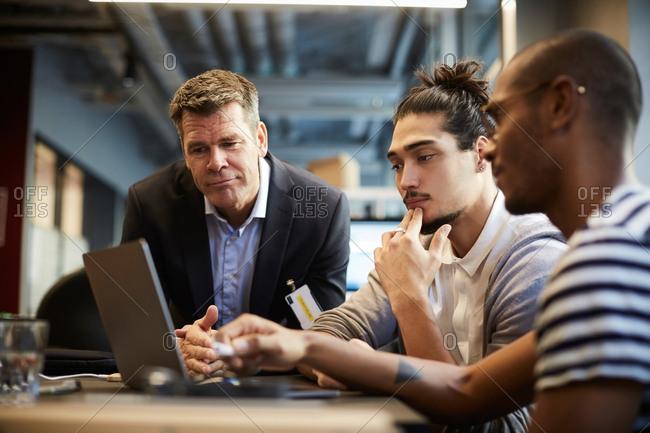 Male entrepreneur giving presentation over laptop at desk in creative office