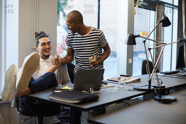 Cheerful creative businessmen greeting each other at desk in creative office